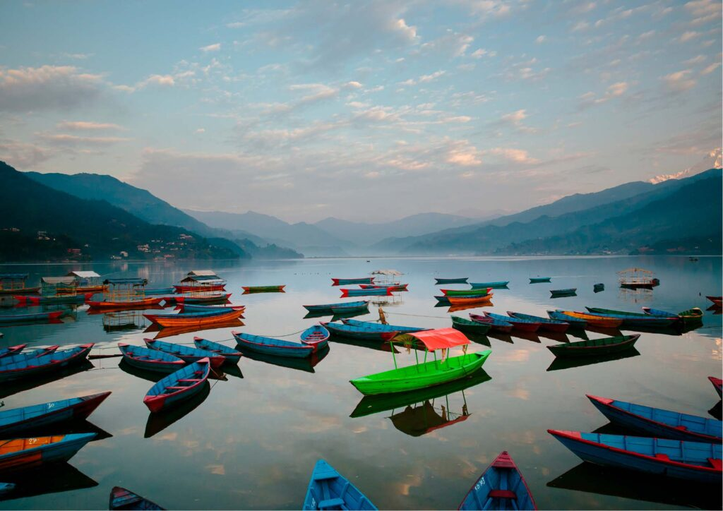Numerose piccole imbarcazioni colorate in legno con le montagne di sfondo